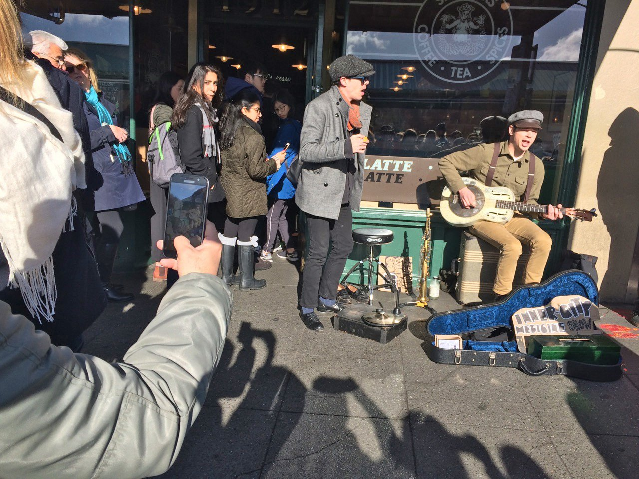 A trio of street musicians sing outside the the original Starbucks store, adding to the easy-going ambience in Pike Place MarketSeattle, Feb 17, 2018